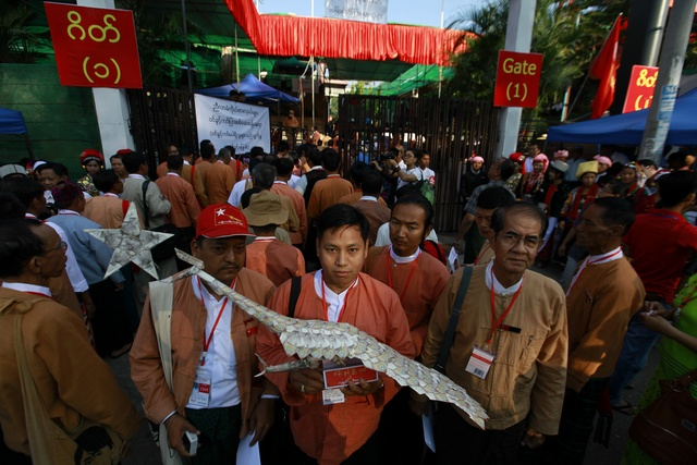 NLD) congress delegates hold the party's emblem of a peacock made with money in Yangon