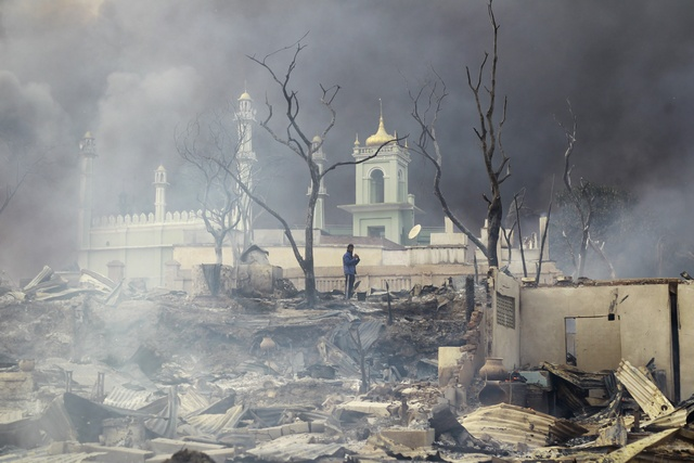 A man stands in front of a mosque as it burns in Meikhtila