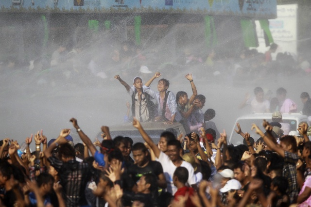People celebrate by getting sprayed with water as they celebrate the Myanmar New Year Water Festival in Yangon