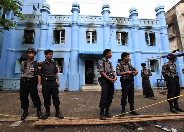 Police stand in front of a mosque and school dormitory that were damaged in a fire in Yangon