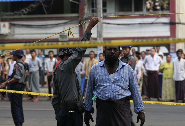A Muslim man walks under a police line near a mosque that was damaged in a fire in Yangon