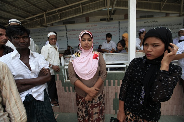 Kyi Kyi San, who lost two sons to a fire at an Islamic school, waits at Yaeway cemetery in Yangon