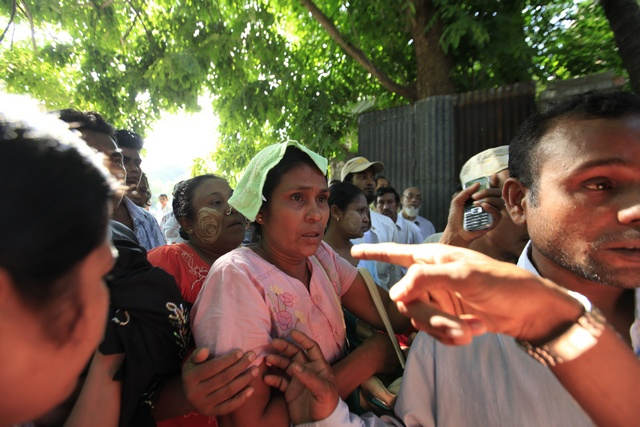 The mother of a boy who died in a fire at an Islamic school arrives at a hospital to see her son's body in Yangon