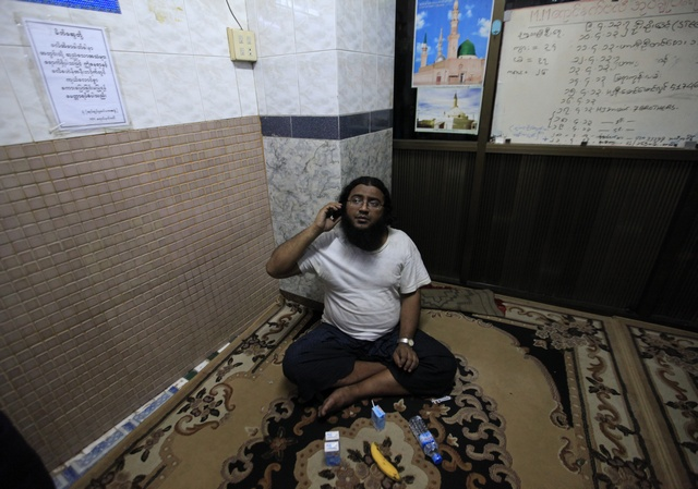 Zayar Phyo, who is in charge of a mosque and a survivor of a fire that damaged it and a school dormitory, talks on a phone in Yangon