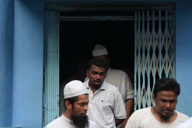 Muslim men exit a mosque that was damaged by a fire in Yangon
