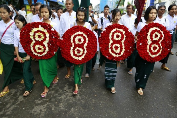 Students hold four wreaths as they march to mark the 25th anniversary of the 8888 protests in Yangon