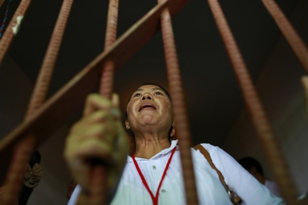 Former political prisoner talks from behind fake cell during demonstration at opening ceremony of memorial and exhibition marking 25th anniversary of the democratic uprising, in Yangon