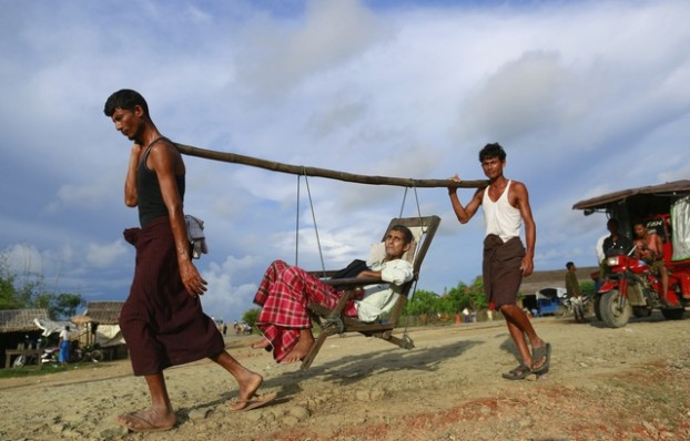 Rohingya men carry a patient to a hospital outside Sittwe