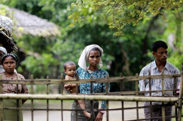 Rohingya Muslims stand near their home in Ohntawgyi village, outside of Sittwe