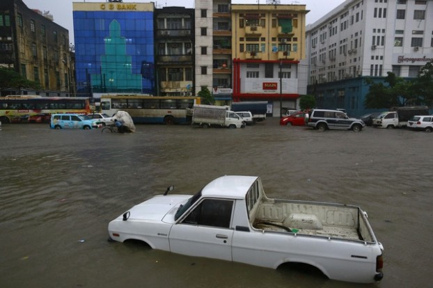 A vehicle is seen next to traffic on a flooded street during rainfall in central Yangon
