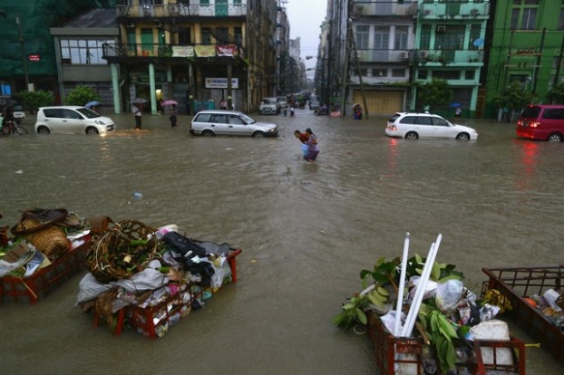 Girls walk along a flooded street during heavy rainfall in central Yangon