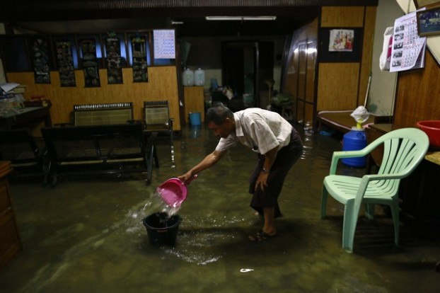 A resident clears out floodwater from his home during heavy rainfall in central Yangon