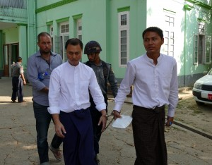 The three defendants, Phil Blackwood (behind), Tun Thurein (left) and Htut Ko Ko Lwin are led to court on 17 March 2015. (PHOTO: DVB)