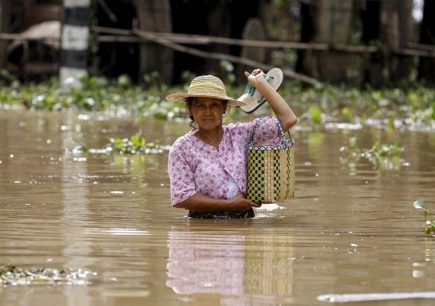 A woman wades through a flooded road in a village at Kawlin township, Sagaing division, Myanmar