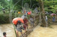 Villagers lug heavy items over an improvised bridge as floods destroy all roads. (PHOTO: DVB).