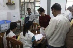 Suu Kyi presents her ID to election officers as she is checked off the voter registrar. (PHOTO: DVB)