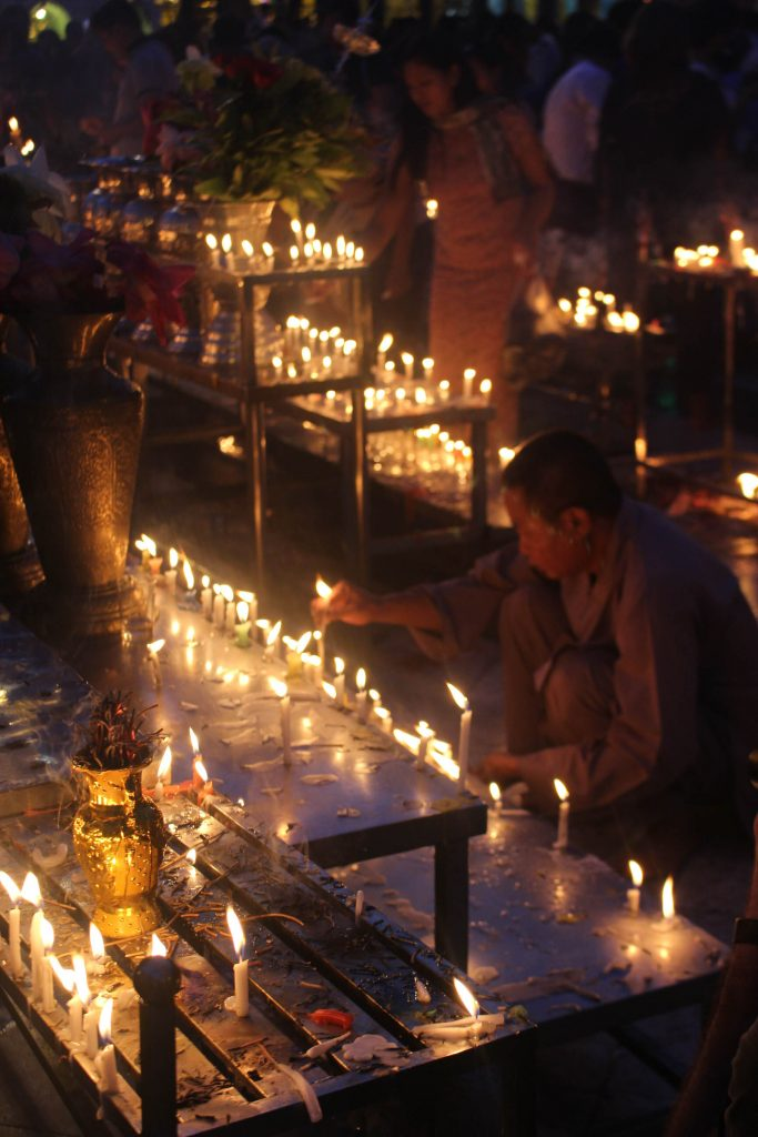 A man surrounded by candles. (Photo: Libby Hogan / DVB)