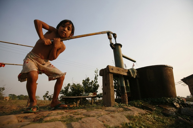 A girl collects water for her bath at a field near Bago