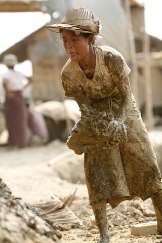 A woman carries mud to shape into bricks at a brick kiln near Hlawga village, north of Yangon