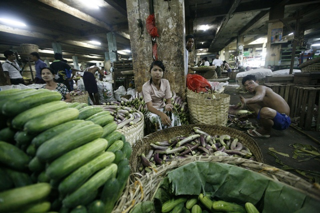 A woman sells cucumber and brinjals at the Thiri Mingalar fruit, flower and vegetable wholesale market in Yangon