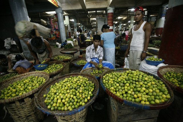 A man sells limes at the Thiri Mingalar fruit, flower and vegetable wholesale market in Yangon