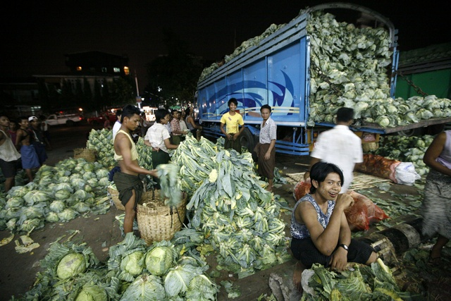 Workers unload cabbage from a lorry at the Thiri Mingalar fruit, flower and vegetable wholesale market in Yangon