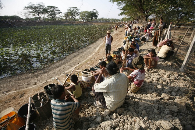 People line up to collect water at a lake in Dala township near Yangon