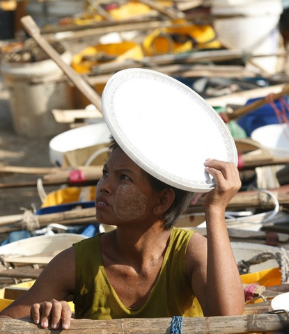 A woman lines up to collect water at a lake in Dala township near Yangon