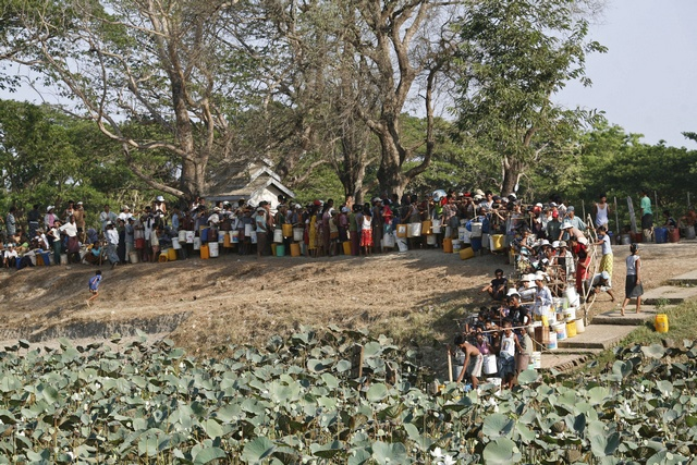 Over a thousand people line up to collect water at a lake in Dala township near Yangon