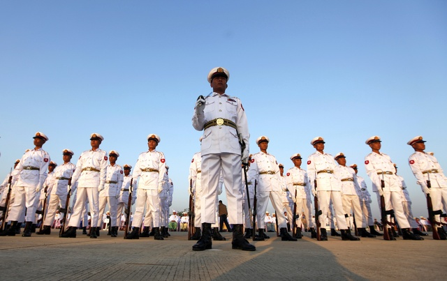 Soldiers stand at attention during a ceremony to mark the 64th Myanmar Union Day in front of the City Hall in the new capital Naypyitaw