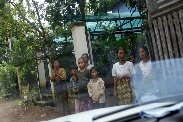 Relatives and neighbours of Thin Hla react as his body is taken away from his home outside Yangon
