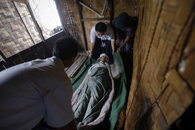 Members of Yangon's Free Funeral Services Society pick the body of a deceased man outside Yangon