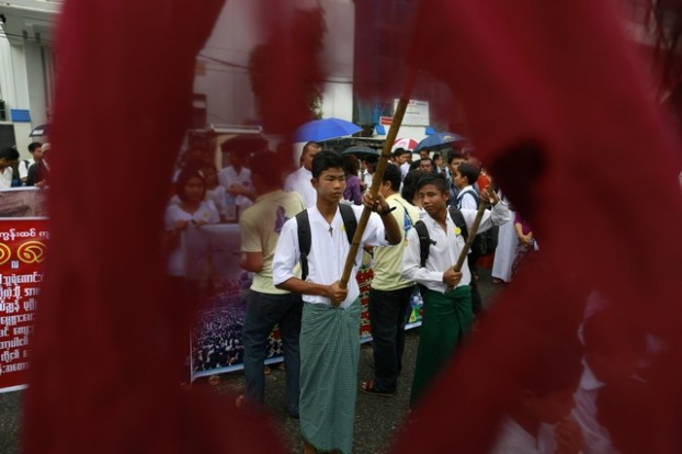 Students march as they wave flags used during the 8888 democratic uprising in Yangon