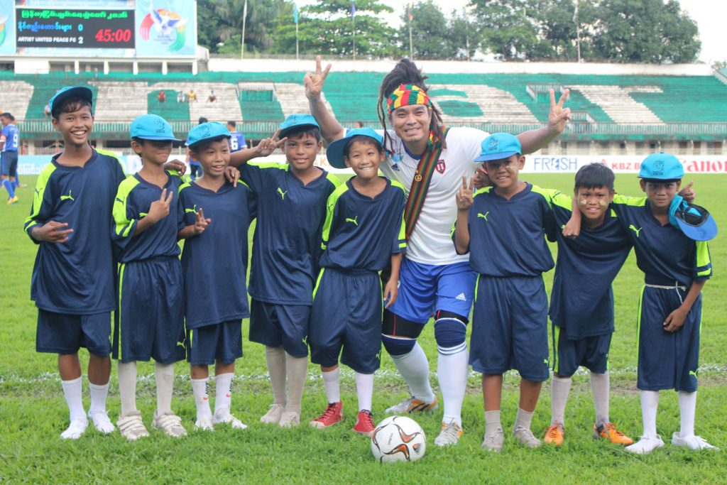 Reggae singer Saw Phoe Kwar with the ball boys from the match. (Photo: Libby Hogan / DVB)