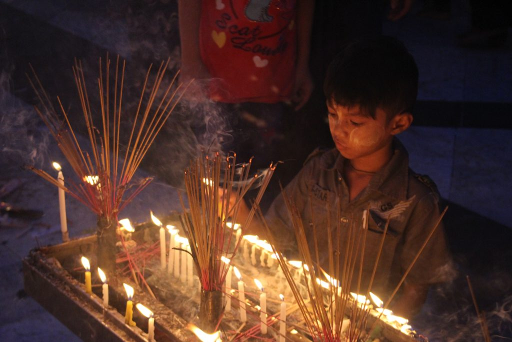 A young boy lights a candle. (Photo: Libby Hogan / DVB)