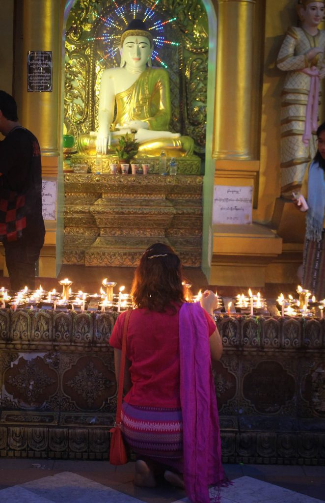 A lady kneels infront of a Buddha statue. (Photo: Libby Hogan / DVB)